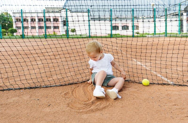 Pouco menina bonito em um t-shirt branco que senta-se na corte de argila do tênis imagens de stock