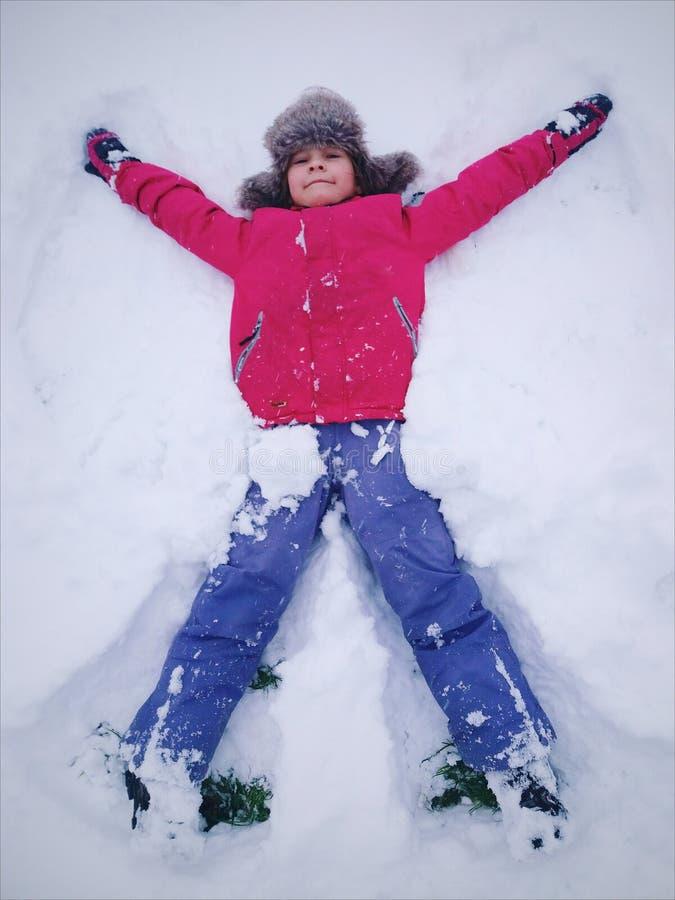 Pouco menina bonito no chapéu forrado a pele do inverno e no sportswear, roupa morna fotografia de stock