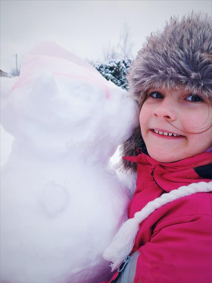 Pouco menina bonito no chapéu forrado a pele do inverno e no sportswear, roupa morna foto de stock