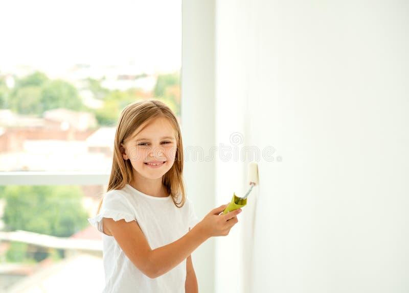 Pouco menina bonito pinta uma parede com rolo de pintura imagens de stock royalty free