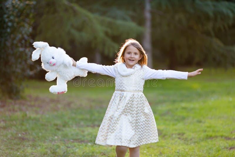 Pouco menina caucasiano com cabelo louro no vestido festivo branco e dourado que corre felizmente para a câmera, riso, guardando  foto de stock