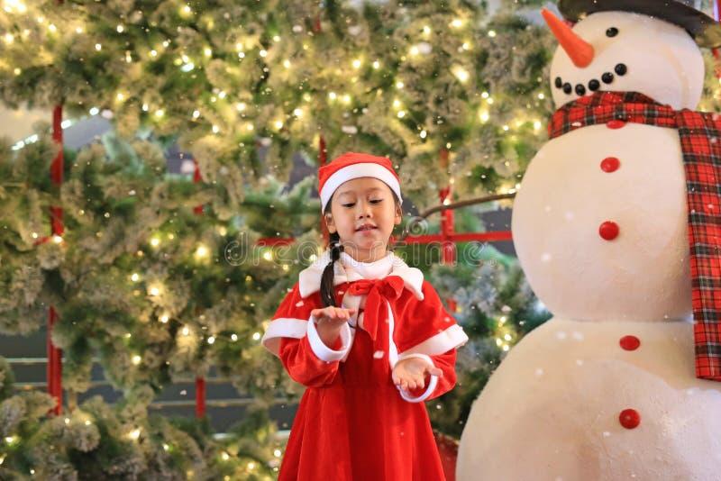 Pouco menina da criança no vestido do traje de Santa no tempo de inverno contra o fundo do Natal Feliz Natal e ano novo feliz imagens de stock royalty free