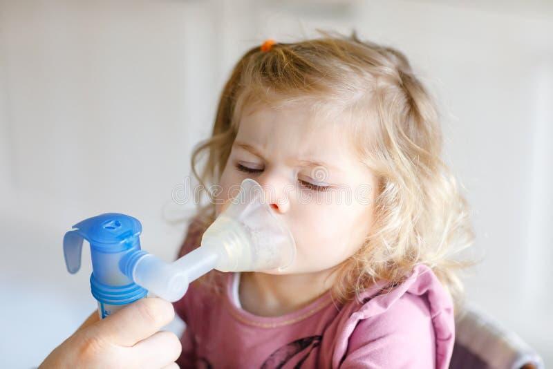 Pouco menina da criança que faz a inalação com nebulizer em casa Pai ou mãe que ajudam e que guardam o dispositivo Criança fotos de stock