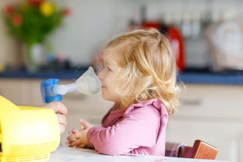 Pouco menina da criança que faz a inalação com nebulizer em casa Pai ou mãe que ajudam e que guardam o dispositivo Criança imagens de stock royalty free