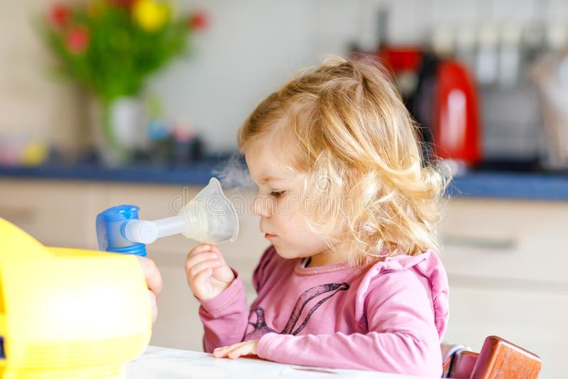 Pouco menina da criança que faz a inalação com nebulizer em casa Pai ou mãe que ajudam e que guardam o dispositivo Criança foto de stock royalty free
