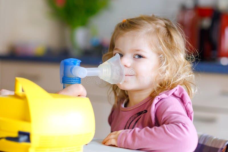 Pouco menina da criança que faz a inalação com nebulizer em casa Pai ou mãe que ajudam e que guardam o dispositivo Criança imagens de stock