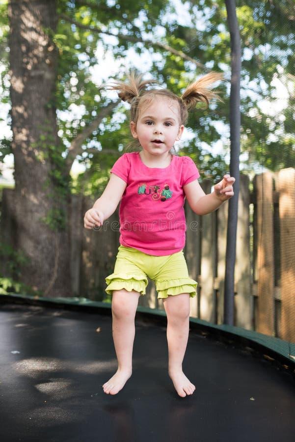 Pouco menina da criança que salta em seu trampolim imagens de stock royalty free