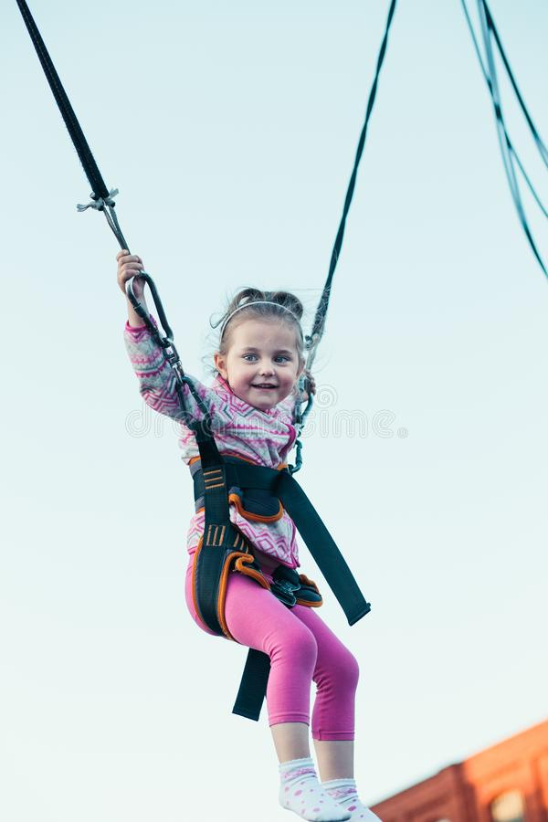 Pouco menina de sorriso adorável que salta no trampolim, tendo o divertimento no funfair imagem de stock royalty free
