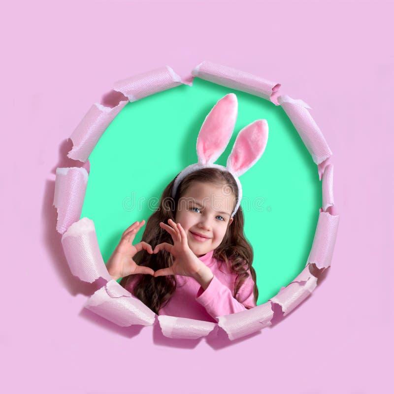 Pouco menina de sorriso com orelhas do coelho mostra o coração em seus dedos fotografia de stock