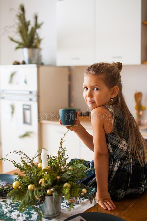 Pouco menina de sorriso que guarda um tampão que senta-se na tabela na cozinha em decorações do Natal fotos de stock