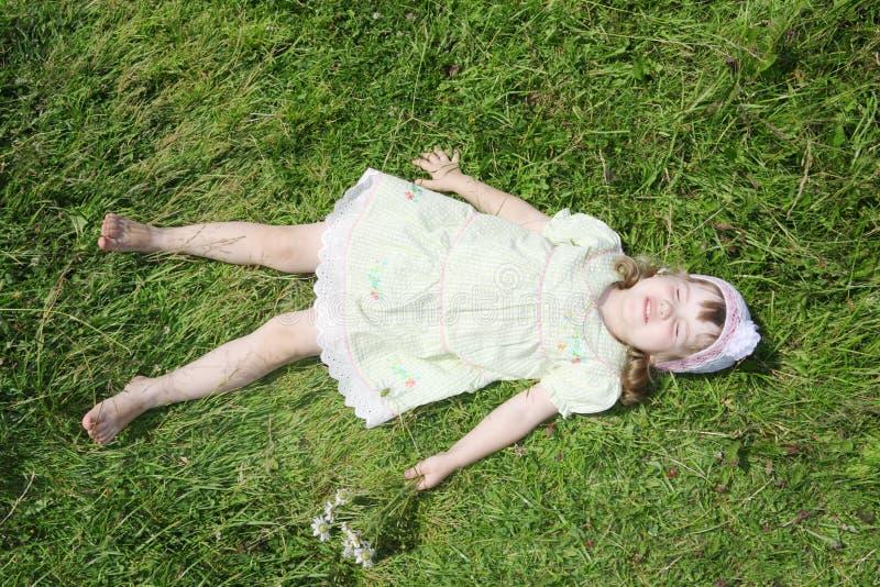 Pouco menina descalça encontra-se na grama verde do prado fotografia de stock