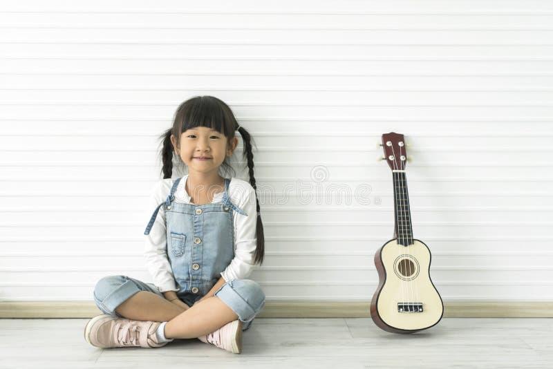 Pouco menina e guita asiáticos bonitos fotografia de stock royalty free