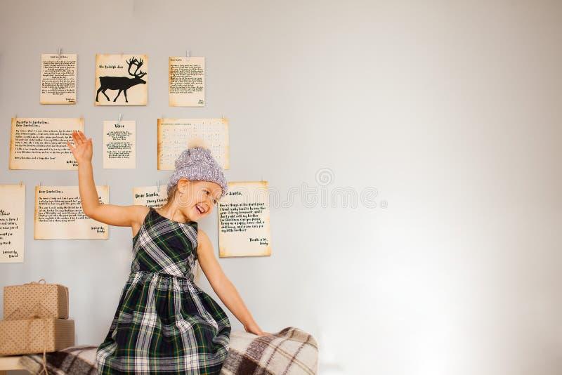 Pouco menina engraçada que senta-se perto da parede cinzenta de Chistmas imagens de stock royalty free