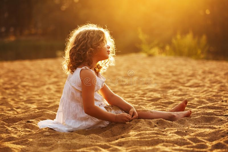 Pouco menina feliz que senta-se e que joga na areia foto de stock