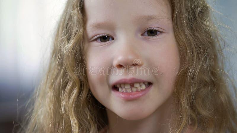 Pouco menina loura bonito que mostra os dentes na câmera, ortodontia das crianças, saúde imagens de stock royalty free