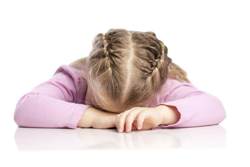Pouco menina loura com tranças encontra-se na tabela Close-up Isolado sobre o fundo branco imagem de stock