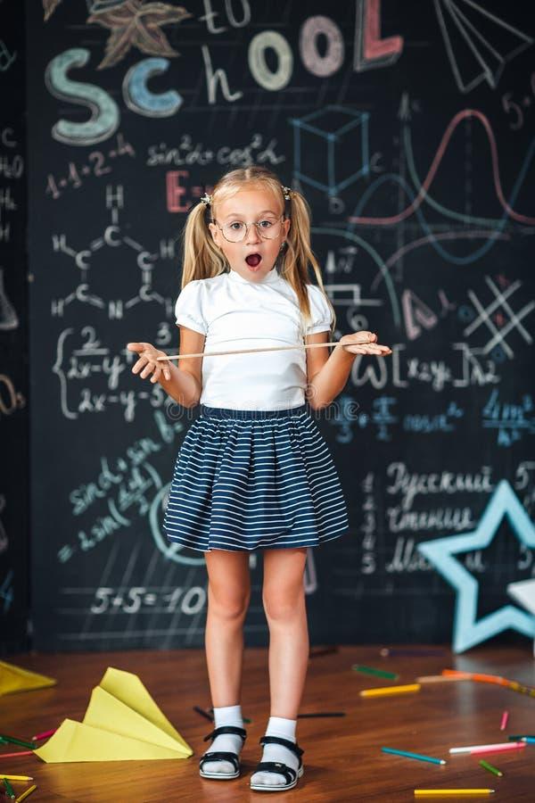 Pouco menina loura com uma cara surpreendida com uma régua em sua menina do aluno das mãos com as réguas grandes contra o quadro  imagens de stock