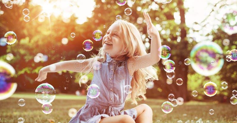 Pouco menina loura entre lotes de bolhas do voo imagens de stock