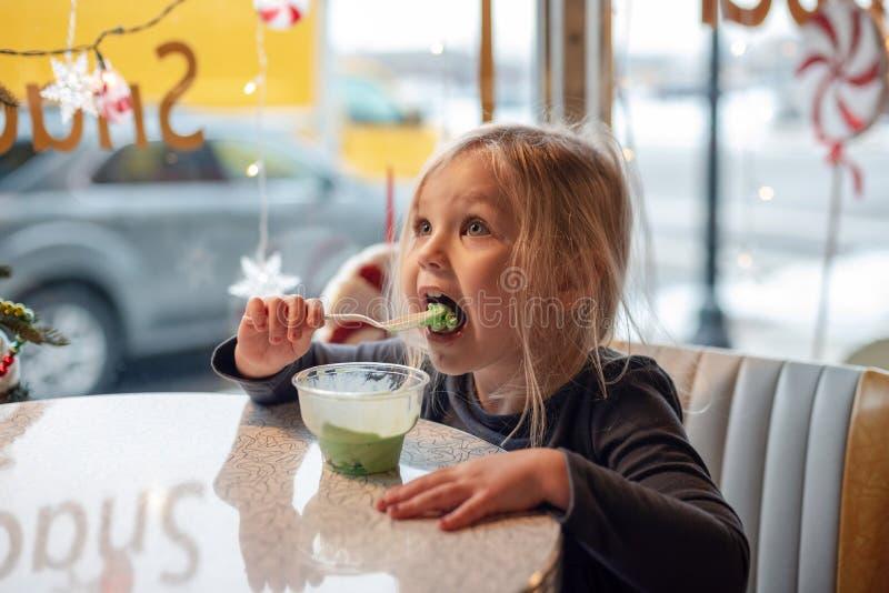Pouco menina loura que come o gelado em um jantar do vintage imagens de stock