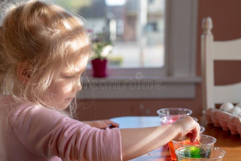 Pouco menina loura que mergulha ovos na tintura para a Páscoa imagem de stock royalty free