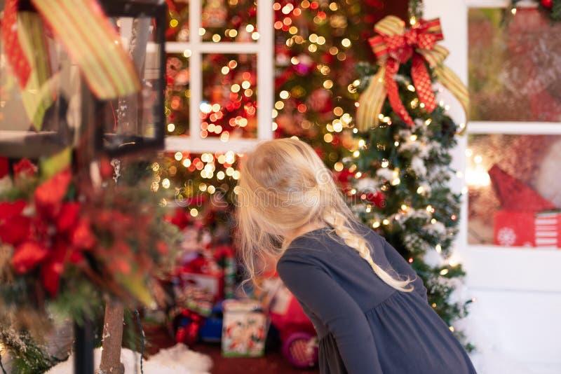 Pouco menina loura que olha luzes e decorações do feriado imagem de stock