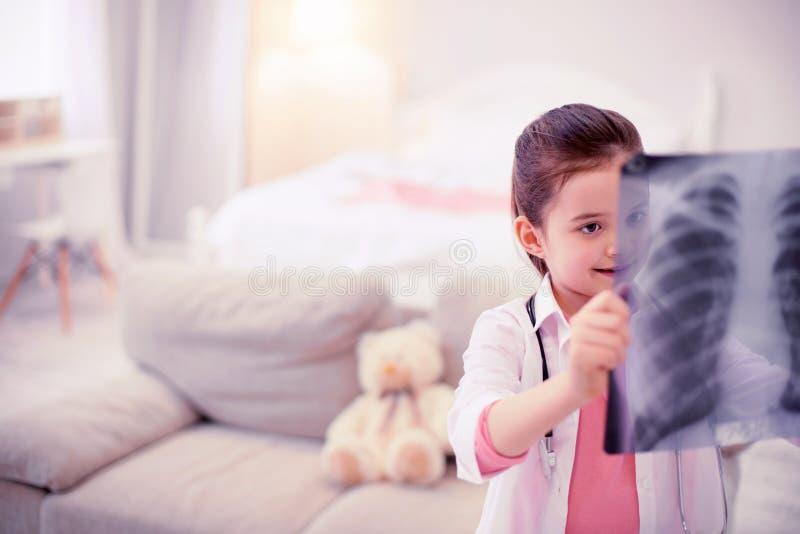 Pouco menina pré-escolar que finge ser um doutor que olha o raio X de sua mamã fotos de stock