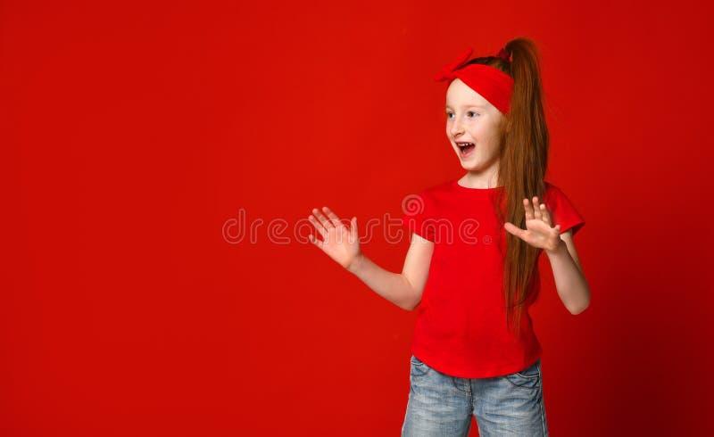 Pouco menina ruivo com uma atadura em seu cabelo em gritos vermelhos de um t-shirt felizmente quando vir algo ao lado foto de stock royalty free