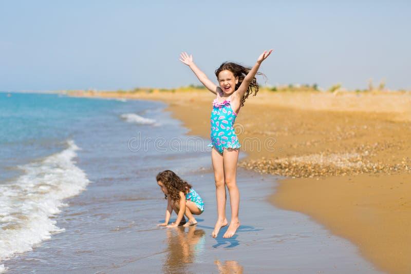 Pouco meninas felizes em roupas de banho brilhantes joga na praia Crian?as em f?rias F?rias de fam?lia Irm?s felizes imagem de stock