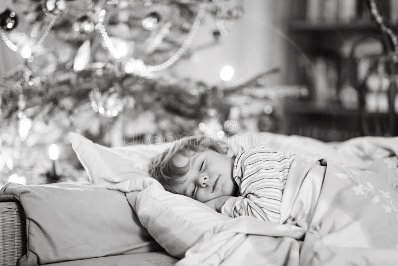 Pouco menino bonito da criança que dorme sob a árvore de Natal fotografia de stock royalty free