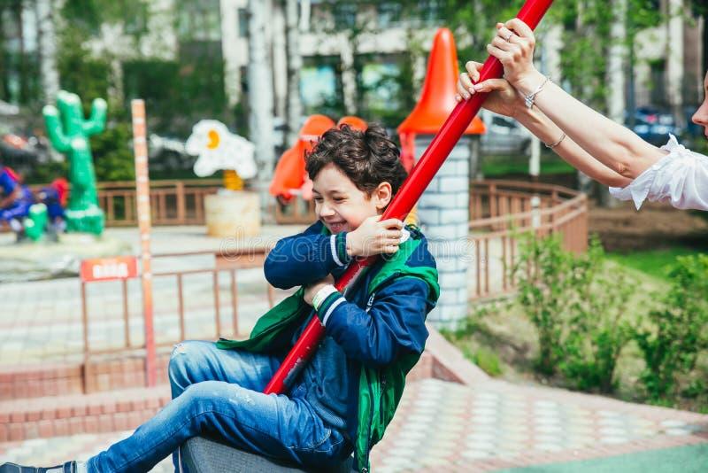Pouco menino bonito está tendo o divertimento exterior Jogo na zona das crianças no parque de diversões fotos de stock royalty free