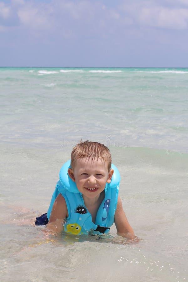 Pouco menino bonito na praia em um revestimento de vida imagens de stock
