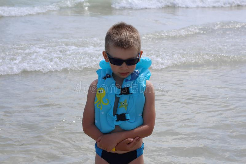 Pouco menino bonito olha infeliz na praia foto de stock