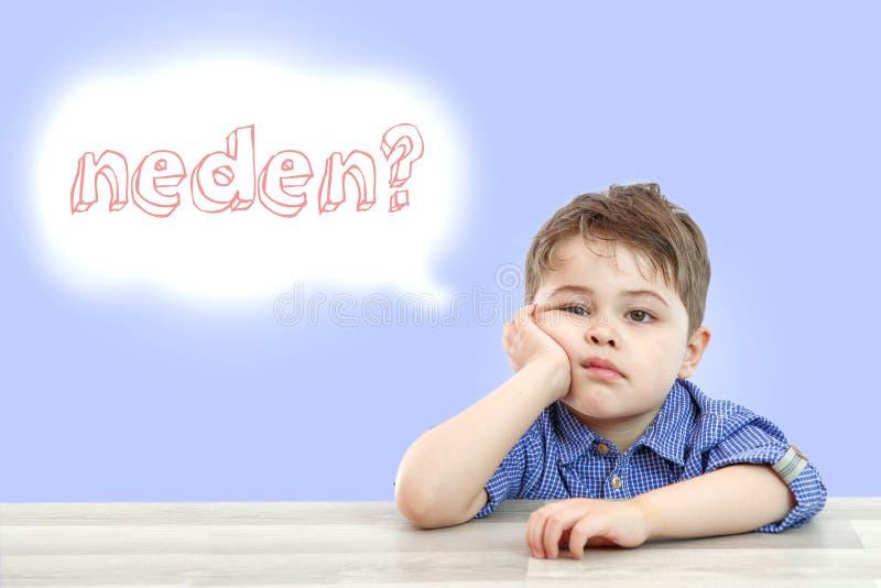 Pouco menino bonito senta-se e pergunta-se por que ? aquele na l?ngua turca em um fundo isolado fotografia de stock