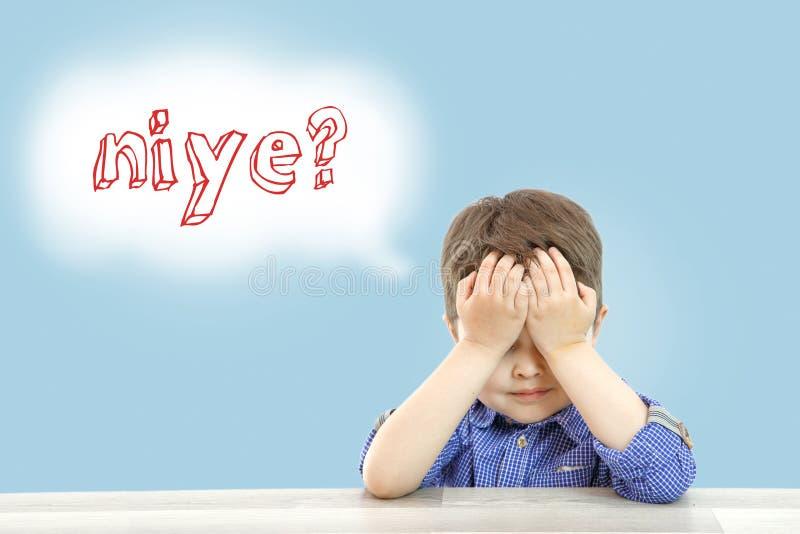 Pouco menino bonito senta-se e pergunta-se porque na l?ngua turca em um fundo isolado foto de stock royalty free