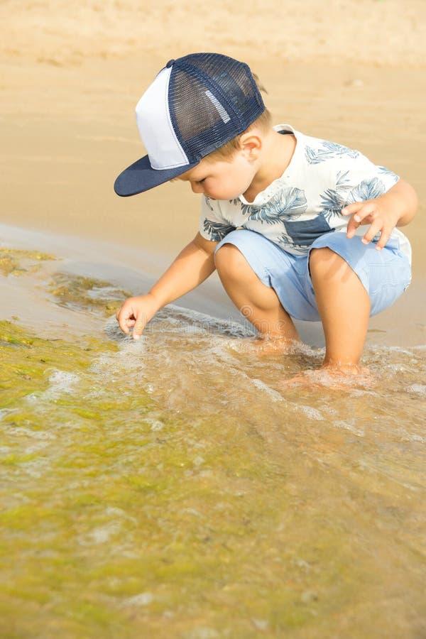 Pouco menino caucasiano bonito da criança com jogos do cabelo louro na praia em ondas do mar no dia de verão ensolarado Férias em imagem de stock
