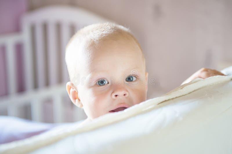 Pouco menino da criança que joga na cama Crian?a bonito que sorri e que esconde sob a tampa Palyful e olhos perniciosos Esconde-e imagem de stock