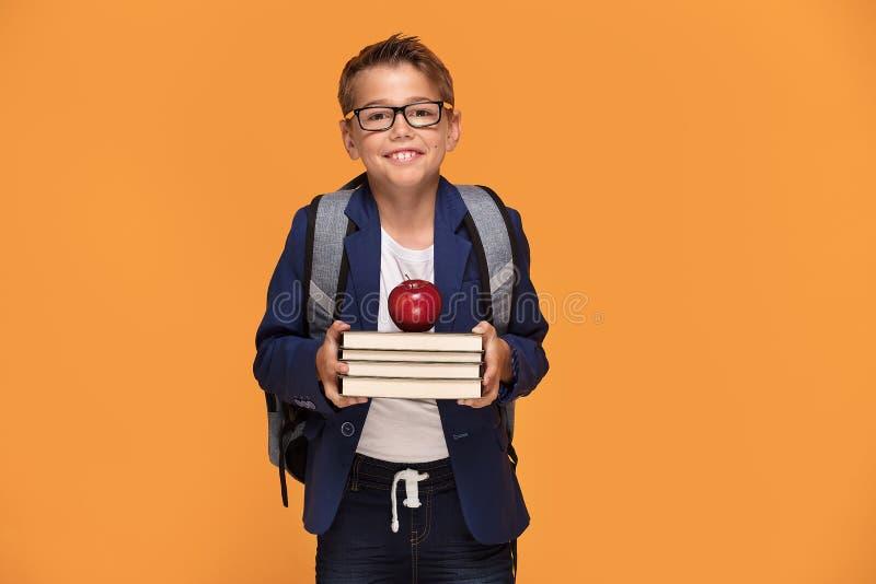 Pouco menino de escola com trouxa e livros fotos de stock