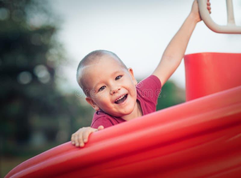 Pouco menino de sorriso em uma corrediça fotografia de stock royalty free
