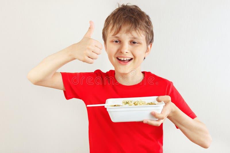 Pouco menino engra?ado em uma camisa vermelha recomenda macarronetes imediatos no fundo branco fotografia de stock royalty free