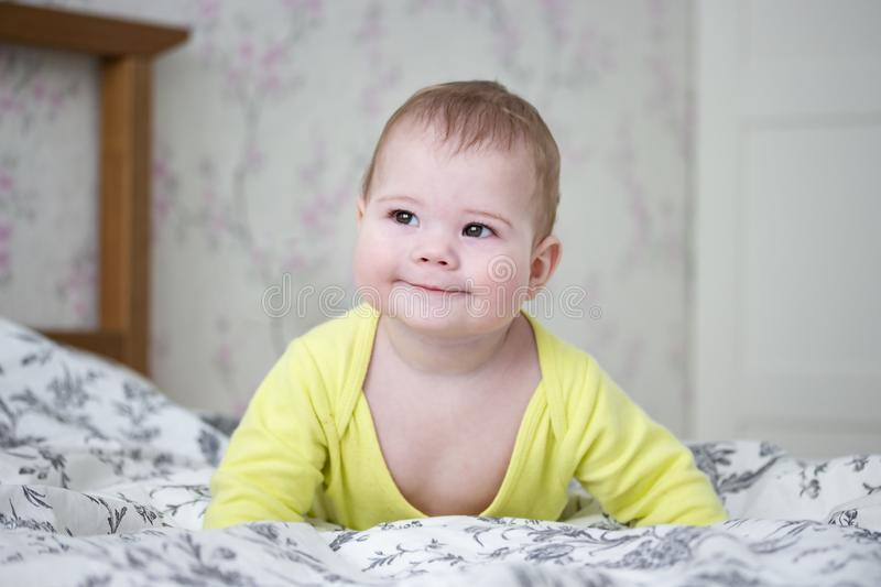 Pouco menino europeu do bebê de 7 meses no amarelo A criança bonito levanta seu corpo em seus braços, sorrisos slyly, é vesgo seu imagens de stock