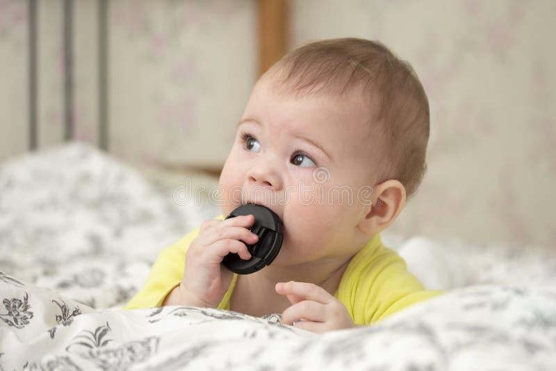 Pouco menino europeu do bebê põe em sua boca o tampão da objetiva Um fotógrafo do principiante por 7 meses encontra-se na cama imagens de stock royalty free