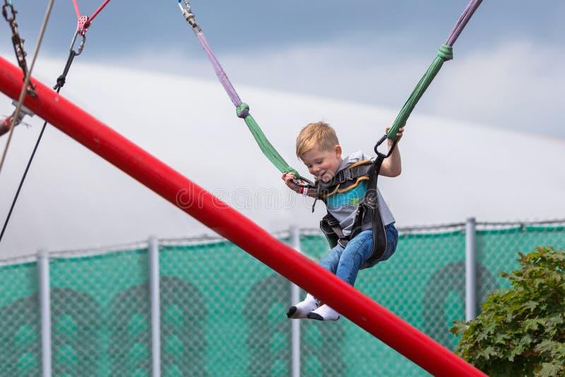 Pouco menino feliz em um parque do trampolim fotos de stock royalty free