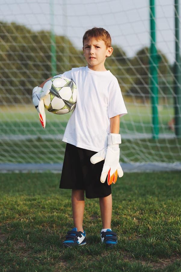 Pouco menino feliz no campo de futebol fotos de stock