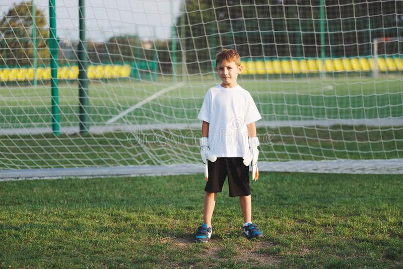 Pouco menino feliz no campo de futebol fotos de stock royalty free