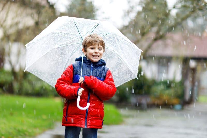 Pouco menino louro da criança na maneira à escola que anda durante o granizo, a chuva e a neve com um guarda-chuva no dia frio imagens de stock royalty free