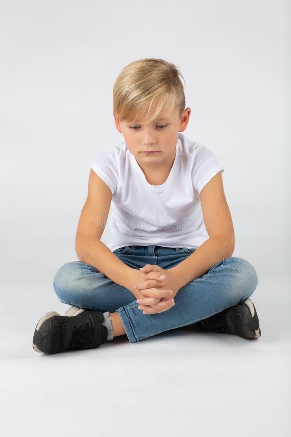 Pouco menino louro está sentando-se no assoalho fotos de stock