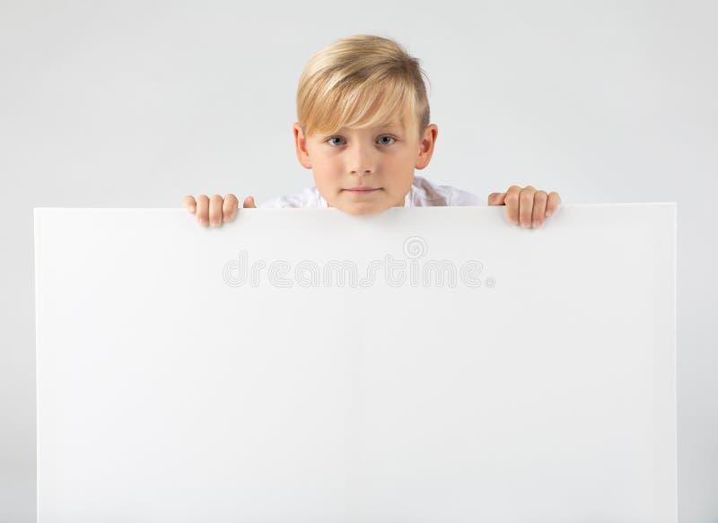 Pouco menino louro guarda um cartaz imagem de stock royalty free