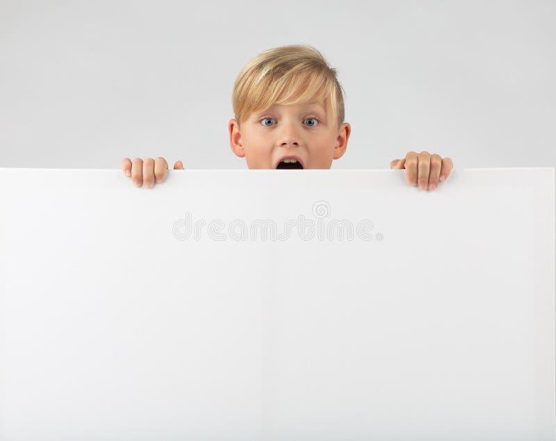 Pouco menino louro guarda um cartaz imagens de stock