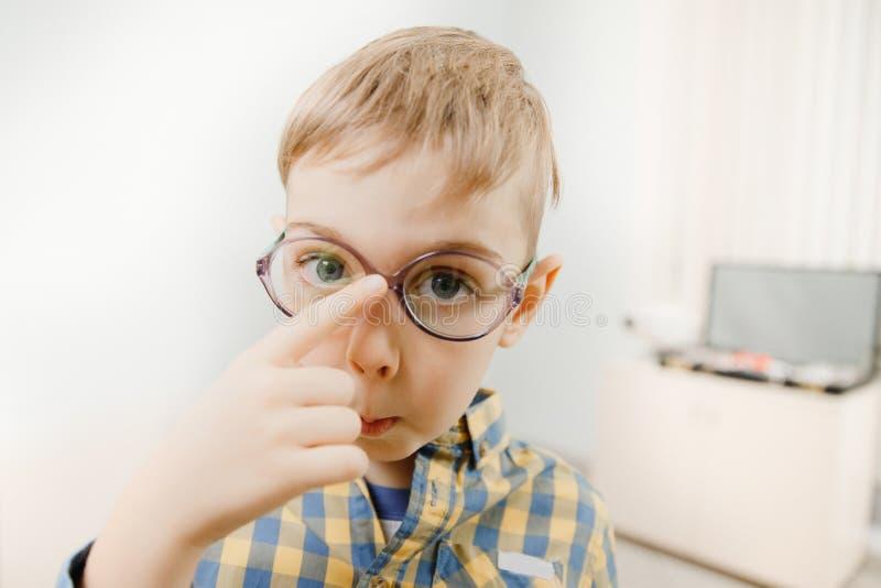 Pouco menino louro na camisa de manta inflou para fora seus olhos azuis grandes foto de stock royalty free
