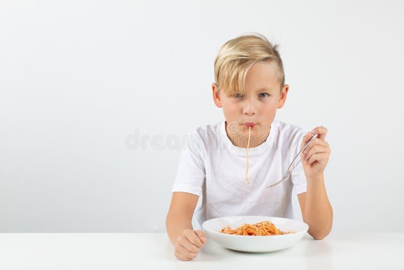 Pouco menino louro na frente do fundo branco come os espaguetes foto de stock